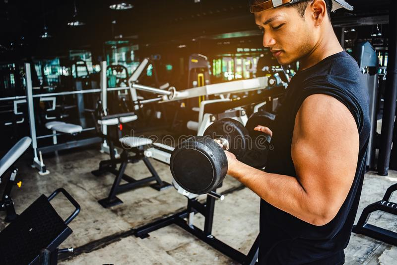 Asian man Bodybuilder with dumbbell weights power handsome athle stock photography