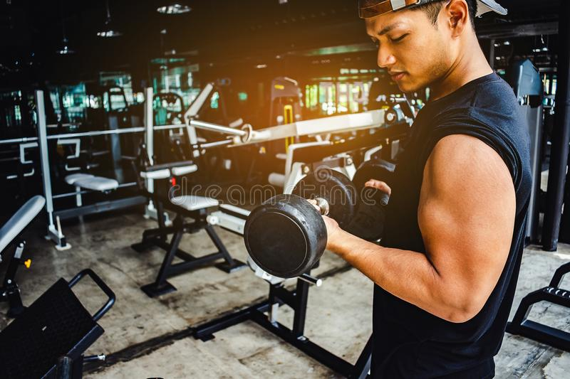 Asian man Bodybuilder with dumbbell weights power handsome athletic exercises.Metaphor Fitness and workout concept exercise royalty free stock photos