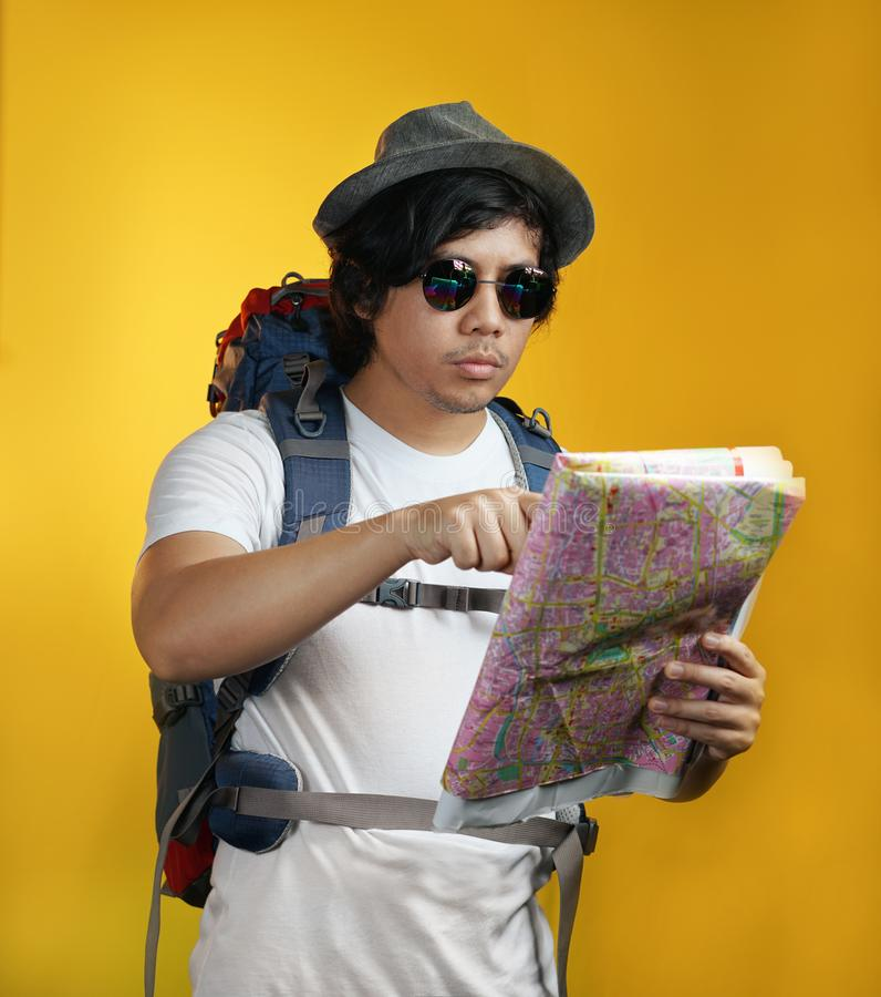 Asian Man Carrying Big Backpack Pointing a Map Against Yellow Ba royalty free stock photo