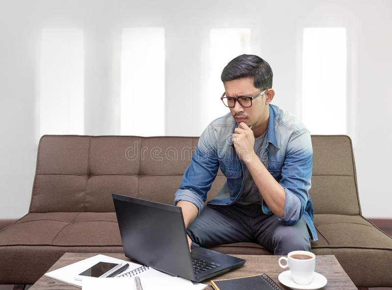 Asian man cencentrate on his work looking at laptop working as a freelance at home royalty free stock photography
