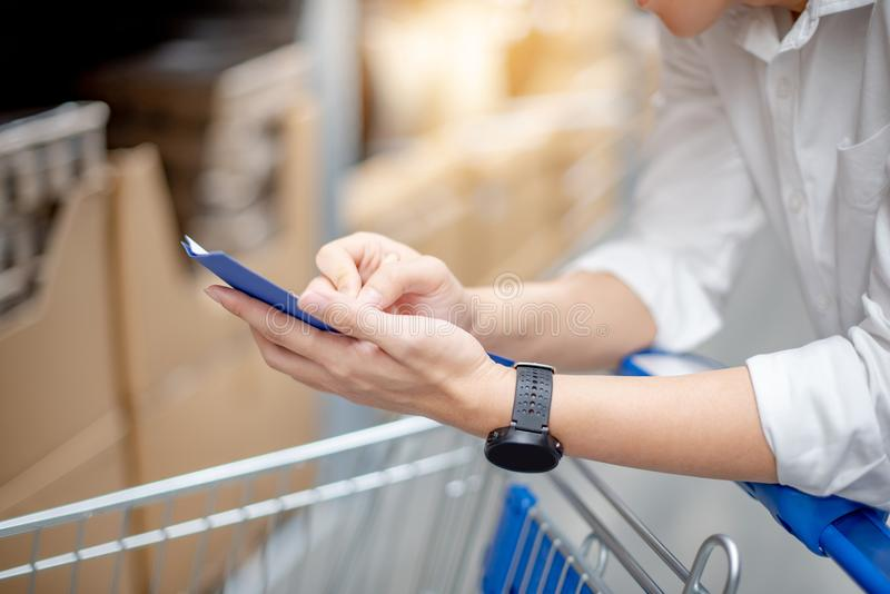 Asian man checking the shopping list in warehouse. Young Asian man standing with cart checking the shopping list in warehouse wholesale, shopping warehousing royalty free stock images