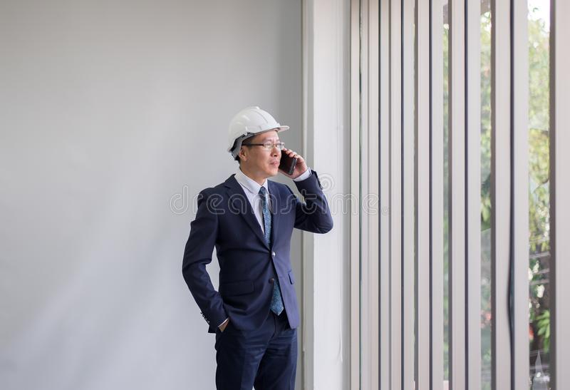 Asian man civil engineer using cellphone and standing in modern office building stock photography