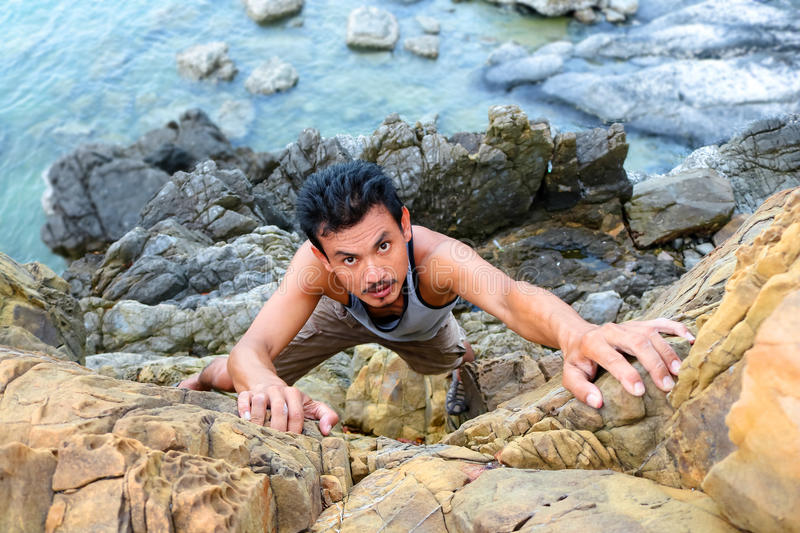 Asian Man climbing rocks near the sea. stock image