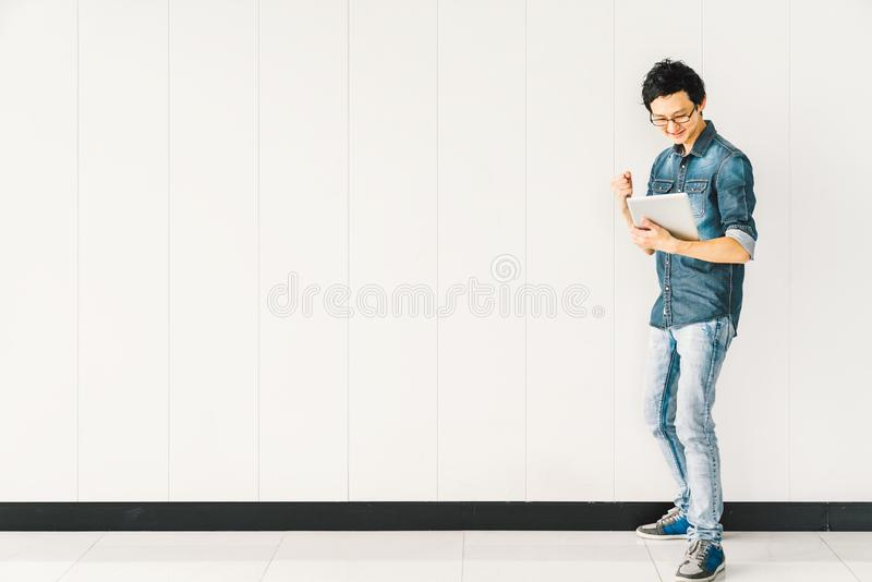 Asian man or college student using digital tablet cheering celebrate success, copy space on white wall background royalty free stock images