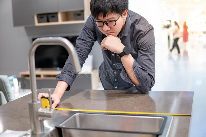 Asian man using tape measure on kitchen counter royalty free stock photo