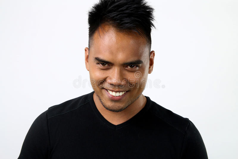 Asian man with a devilish look. Young man with a devilish look on a white background royalty free stock image