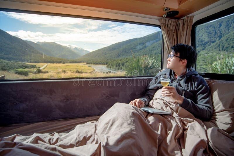Asian man drinking beer in camper van stock photos