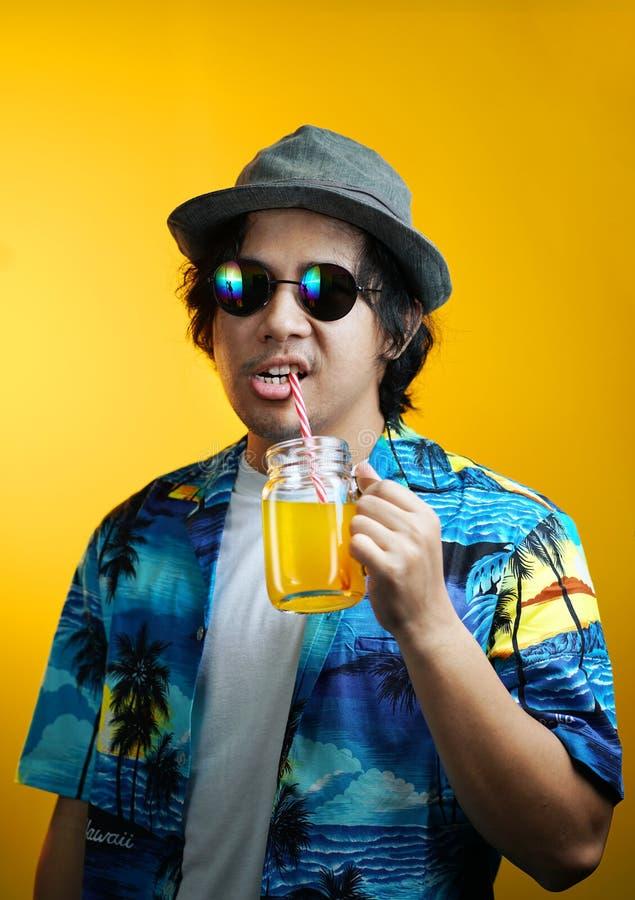 Asian Man Drinking Orange Juice Wearing Fedora Hat and Sunglasses against Yellow Background stock photo