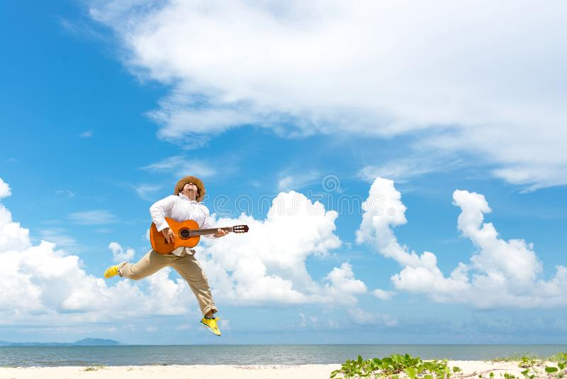 Asian man enjoying summer, playing classic guitar and jumping on the beach in vacations, blue sky background stock photo