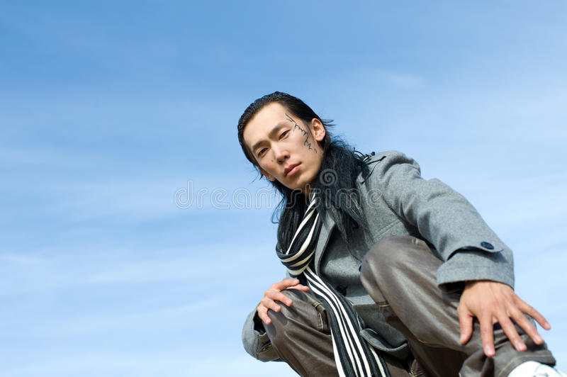 Asian man of fashion. Young asian man in grey coat and striped black-and-white scarf. The tracery on his cheek is his name Chinghis in ancient Mongolian royalty free stock images