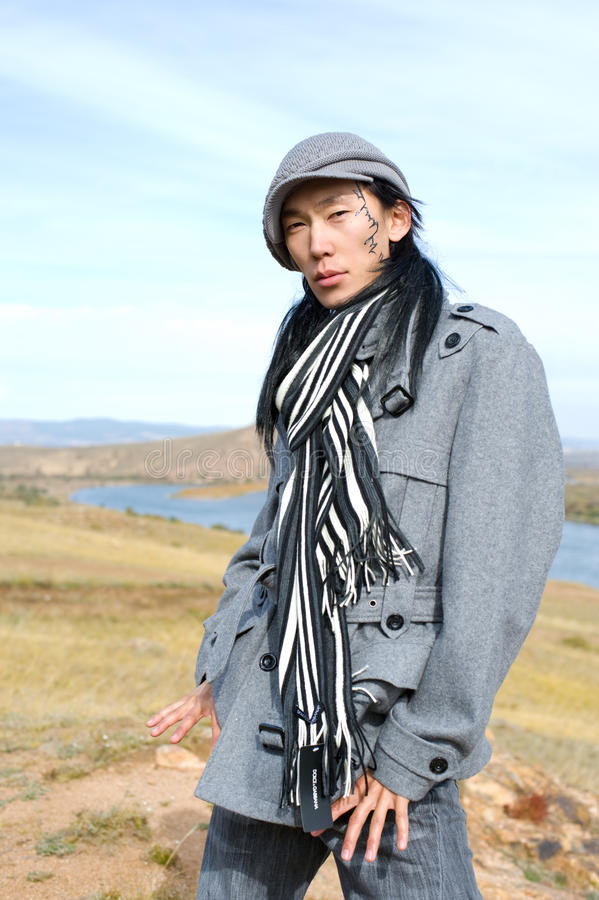 Asian man of fashion. Young asian man in grey coat, cap and striped black-and-white scarf. The tracery on his cheek is his name Chinghis in ancient Mongolian stock photo