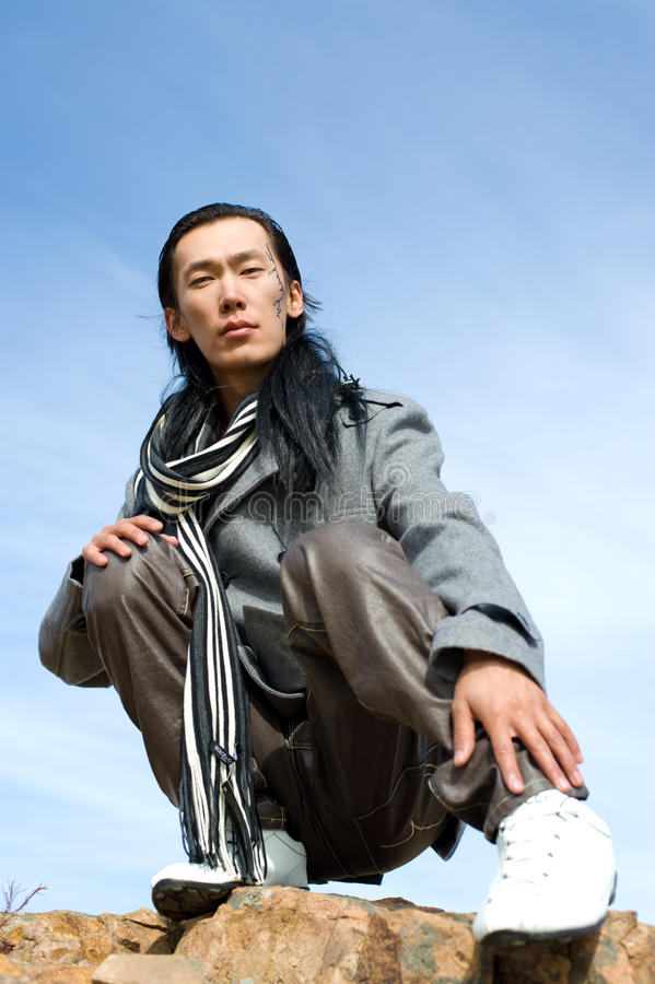 Asian man of fashion. Young asian man in grey coat and striped black-and-white scarf. The tracery on his cheek is his name Chinghis in ancient Mongolian stock photo