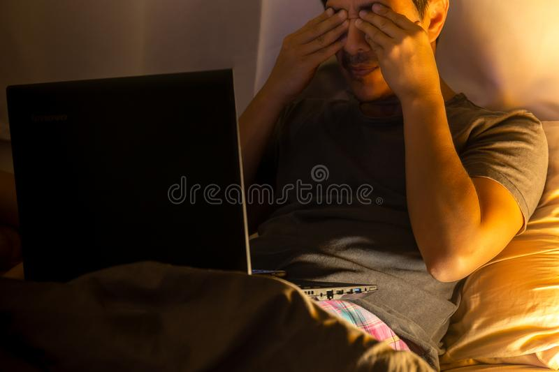 Asian man feeling stressed working with laptop computer in bed at night. stock photos