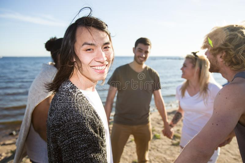 Asian man with friends on beach royalty free stock photography