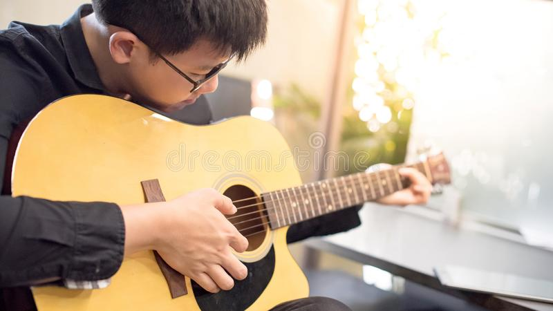 Asian man guitarist playing music with guitar royalty free stock images