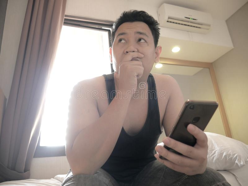 Asian man having bad news on phone when waking up on bed in the morning royalty free stock photos