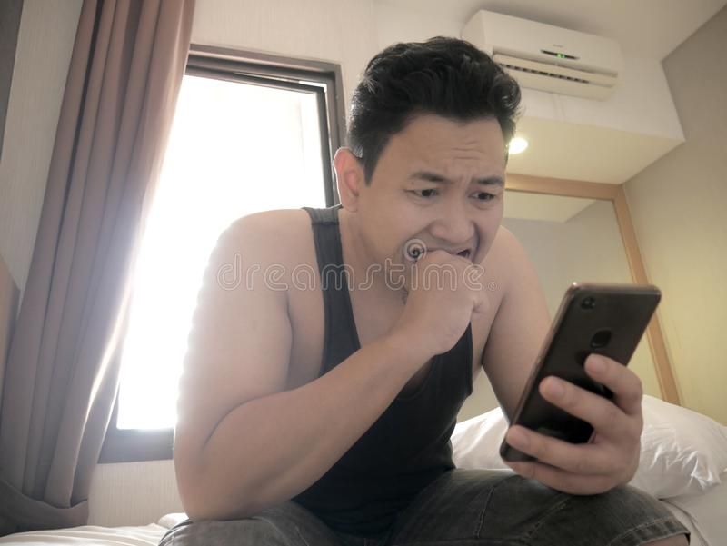 Asian man having bad news on phone when waking up on bed in the morning royalty free stock images