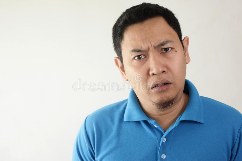 Asian Man Having Skeptical and Dissatisfied or Distrust Expression. Portrait of young Asian man looking skeptical, dissatisfied, or distrust expression, looking royalty free stock images