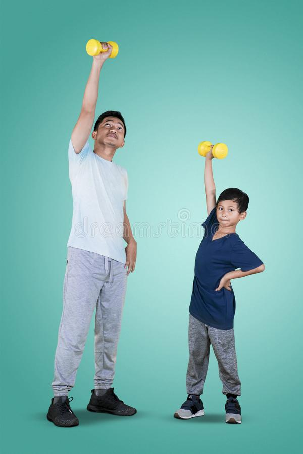 Asian man with his son lifting a dumbbell stock photography