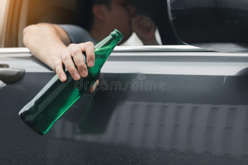 Asian man holding a bottle of beer outside the car while driving royalty free stock image