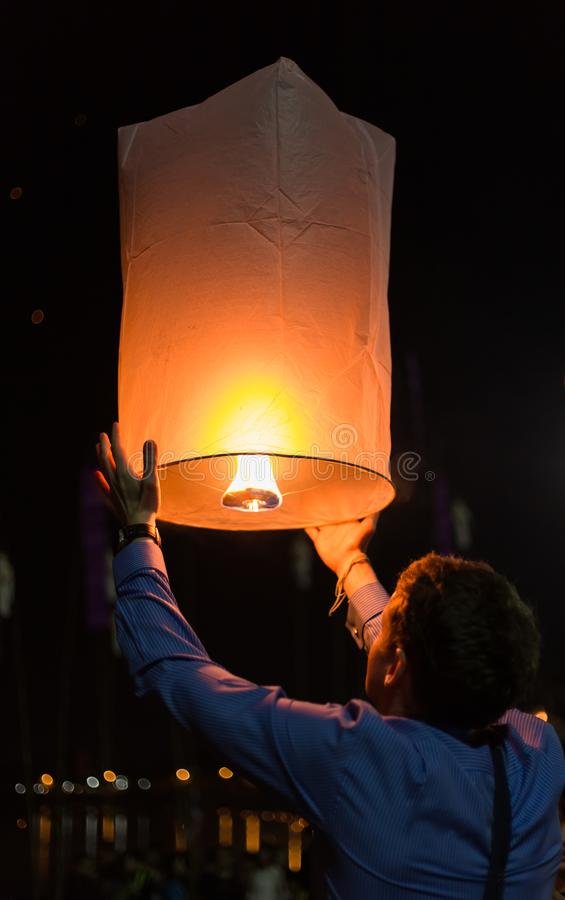 Asian man holding floating sky lanterns during Loy Kratong Festival stock image