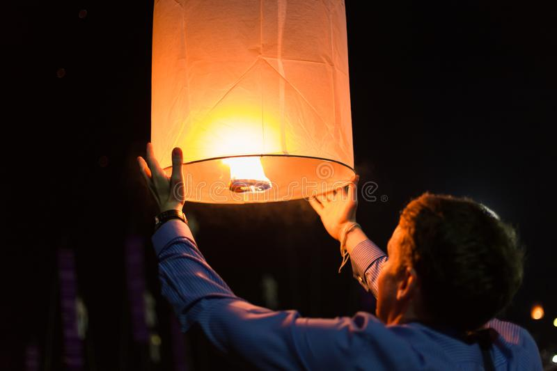 Asian man holding floating sky lanterns during Loy Kratong Festival stock photo