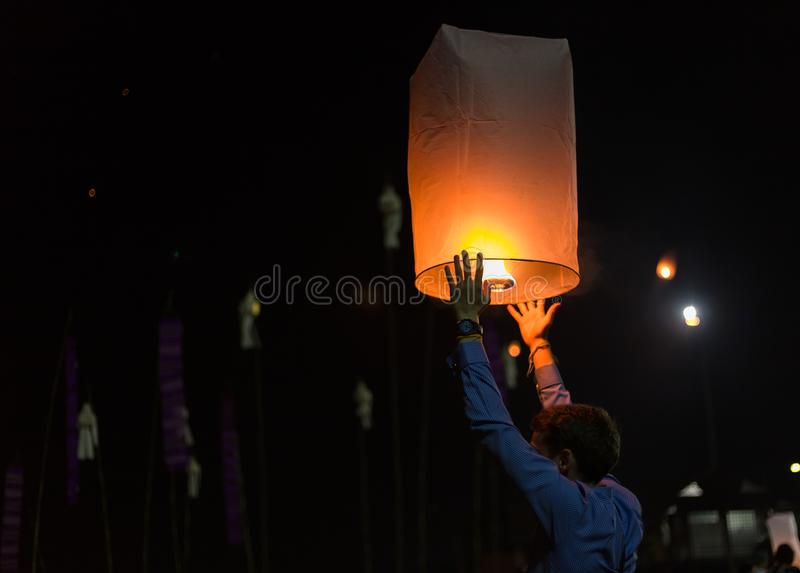 Asian man holding floating sky lanterns during Loy Kratong Festival royalty free stock photo