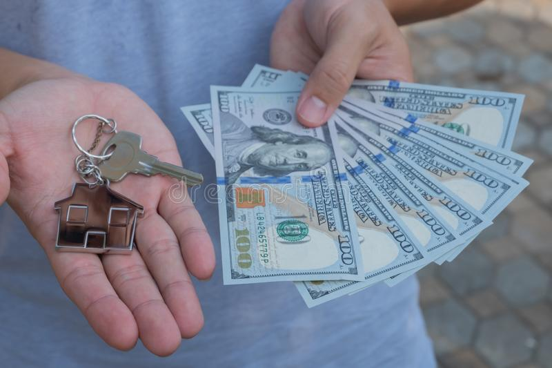 Asian man holding one hundred dollar bills and home shape key chain. Property investment and mortgage finance concept royalty free stock image