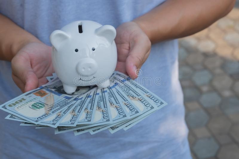 Asian man holding one hundred dollar bills with together with white piggy bank. Wealthy and richness concept royalty free stock photography