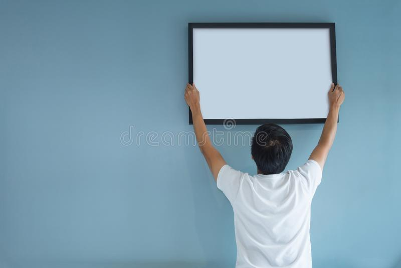 Asian man holding a picture frame on blue wall. royalty free stock image