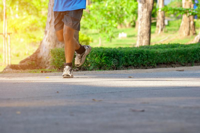 Asian Man jogging through a park on sunny day. Running and Healthy lifestyle concept. stock photos