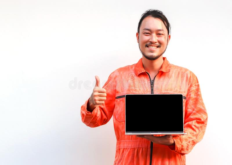 Asian man in jumpsuit standing on white background holding computer laptop turning  black screen to camera  and showing his thumb stock photo