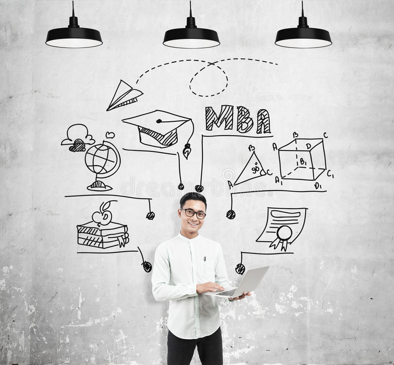 Asian man with laptop and MBA sketch. Asian man with laptop standing near concrete wall with MBA sketch on it. Concept of business education stock image