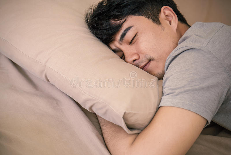 Asian man laying on bed, deep in sleep. Young asian man with attractive smile laying on bed indoors Portrait of man in bedroom royalty free stock images