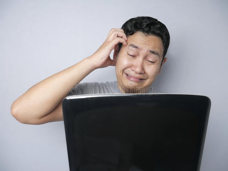Asian Man Looked Regret and  Disappointed Expression Looking at Laptop stock photo