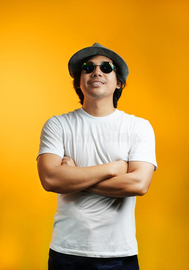Asian Man Looking up with Arms Crossed Wearing Sunglasses and Fedora Hat royalty free stock image