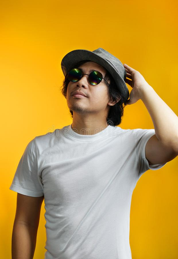 Asian Man Looking up and Holding His Head Wearing Sunglasses and stock image