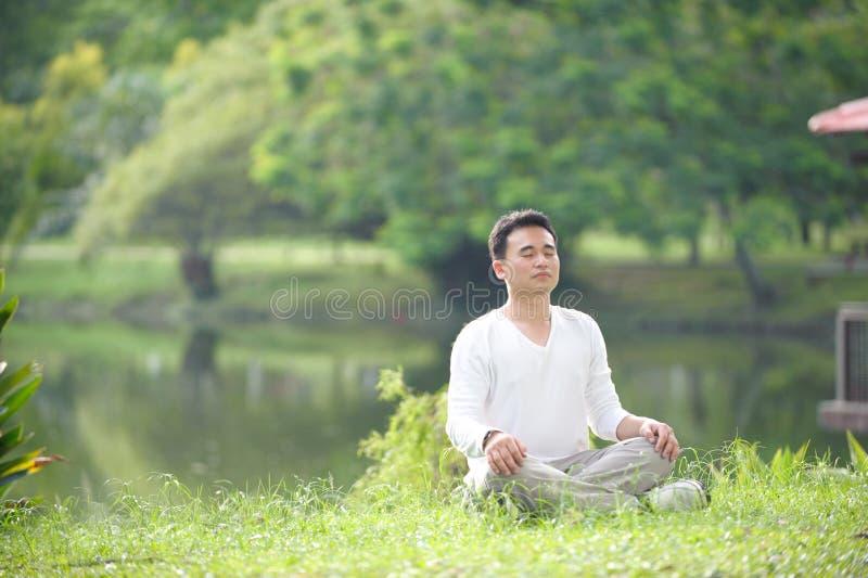 Asian Man Meditating. In the park stock photos