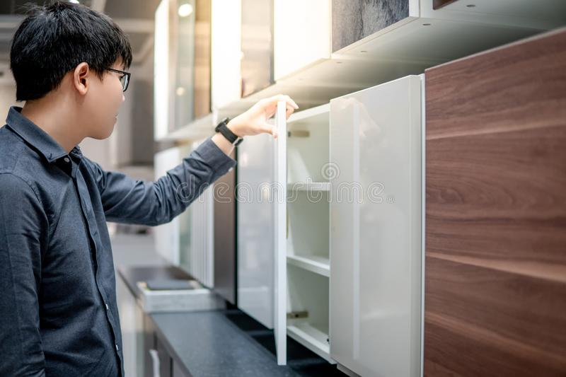 Asian man opening cabinet in furniture store royalty free stock images