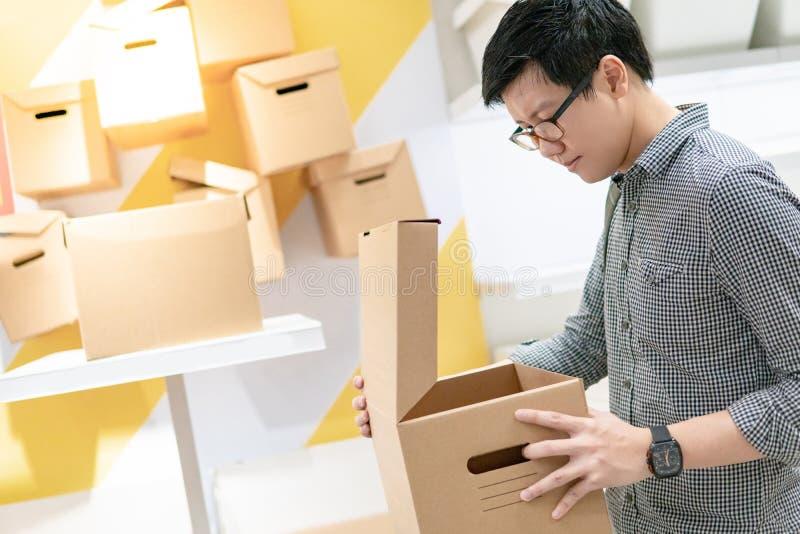 Asian man opening cardboard box package stock photo
