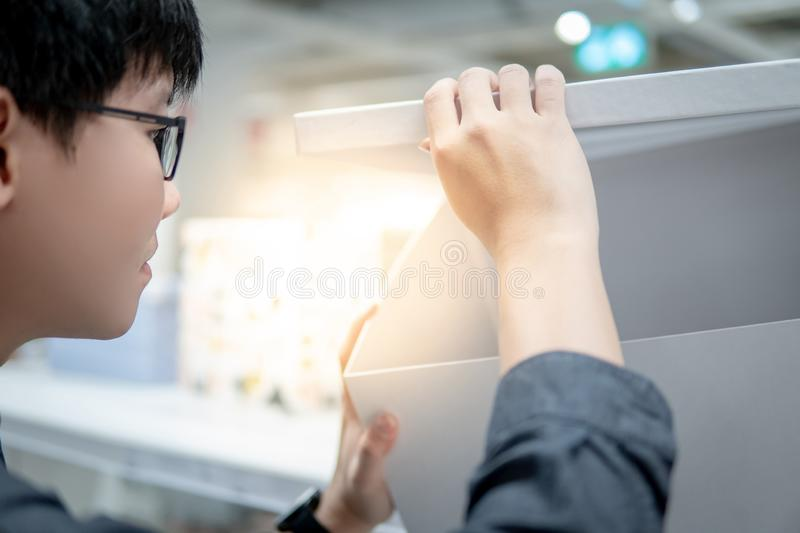 Asian man opening white paper box. Asian man opening empty white paper box in grocery store. Packaging design for home decoration. Unboxing concept stock images