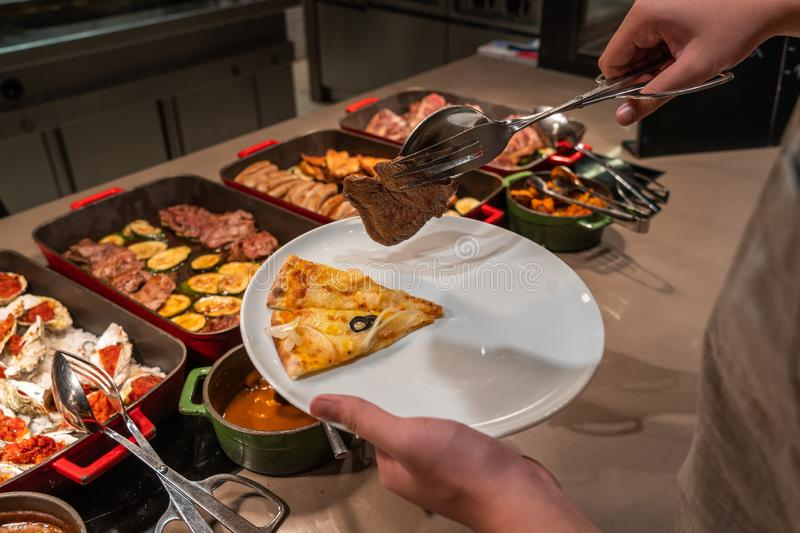 Asian man picking pizza and grilled meat in buffet meal. Asian man using tongs and picking pizza and meat in buffet royalty free stock images