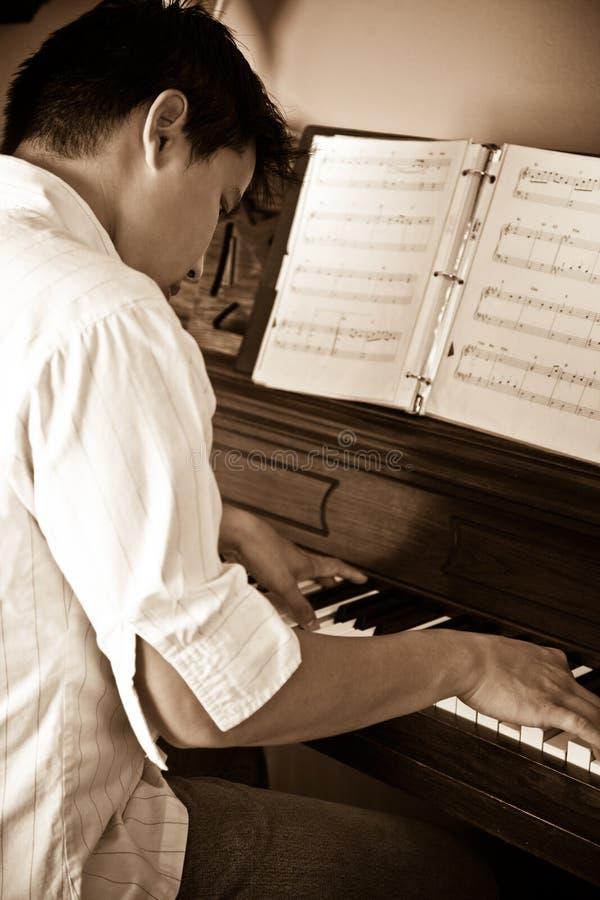 Asian man playing piano stock photos