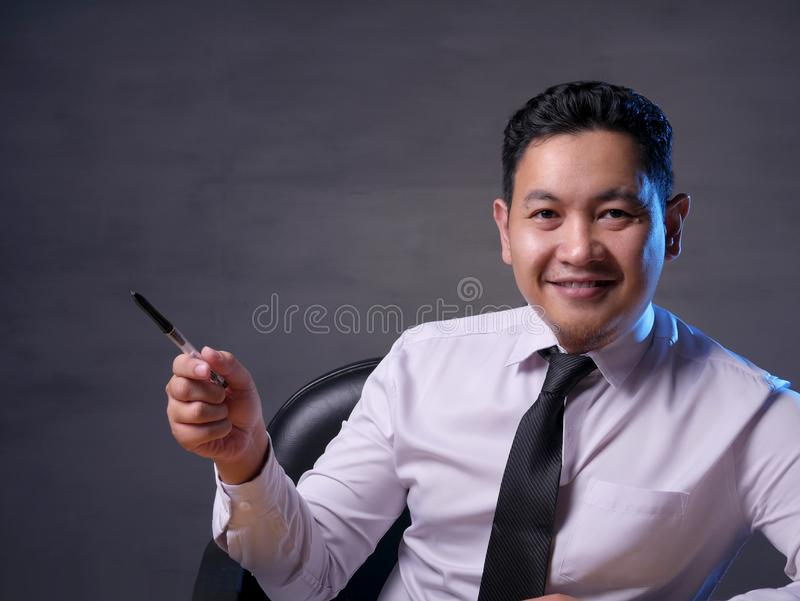 Asian Man Presenting Something on His Side with Copy Space stock photo
