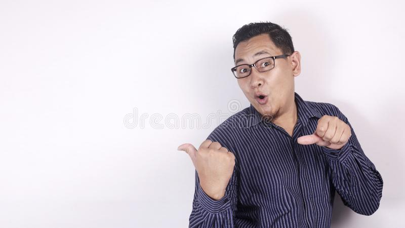 Asian Man Presenting Something on His Side with Copy Space royalty free stock photo