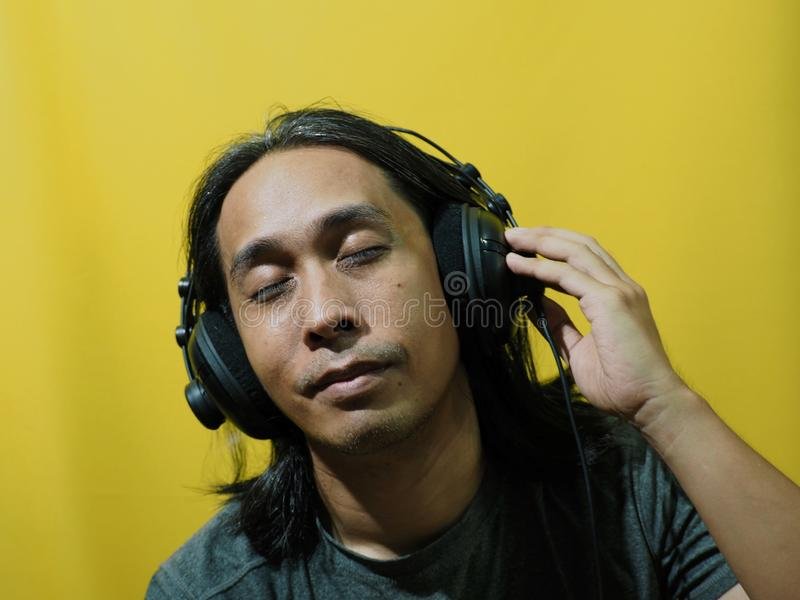 Asian man put on headphone on yellow background stock images