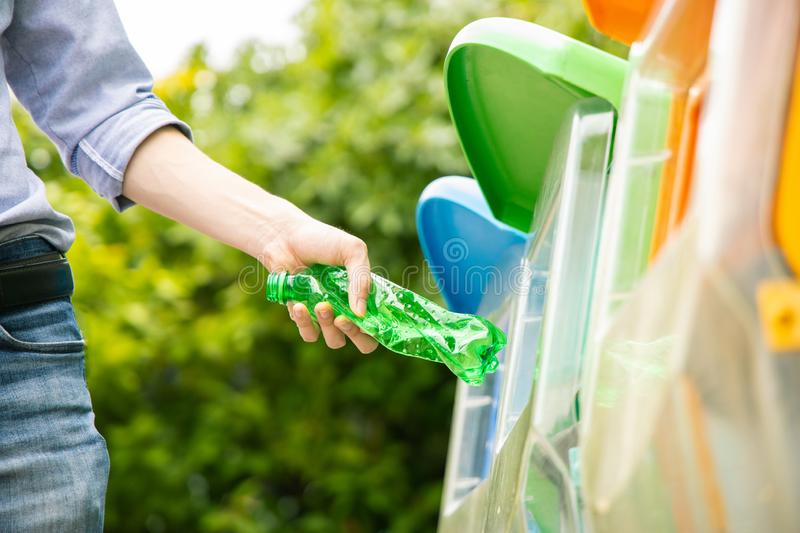 Asian man put plastic bottle into bin. Asian male putting twisted green plastic bottle into recycle bin in park stock images