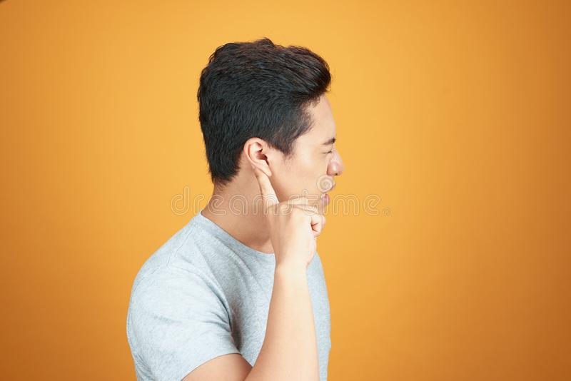 The Asian man raised his ears to the hearing with his hand.  stock image
