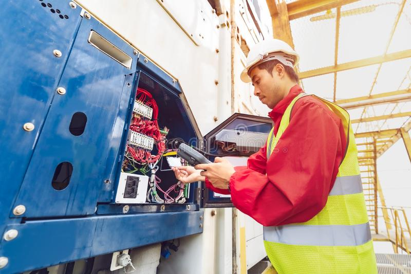 Asian man reefer technician is seriously working and monitoring reefer container at the port. Engineer checking equipment. In control system of reefer container stock image