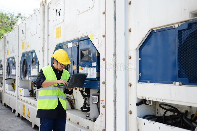 Asian man reefer technician is seriously working and monitoring reefer container. At the port stock photos